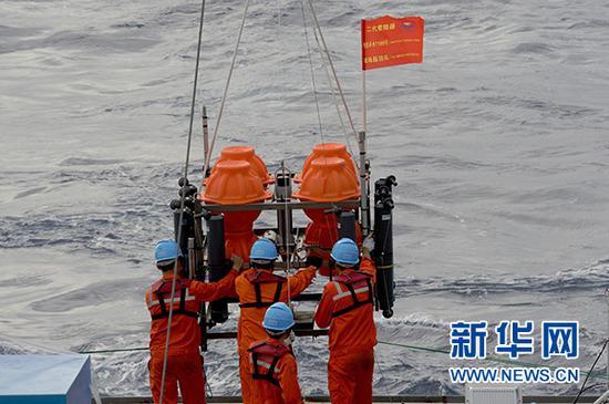 """考察队员将负责采集海水的""""彩虹鱼""""第二代着陆器布放到海里"""