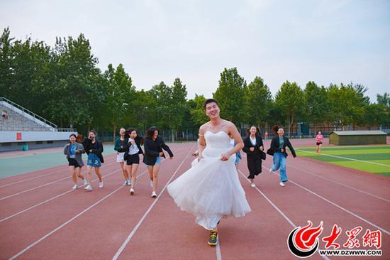 班长王玉华(前)穿上婚纱照和同学拍摄合影