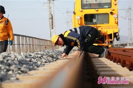 作业人员俯身查看钢轨高低方向。