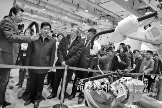 博览会上,有关领导参观济南制造的工业机器人.