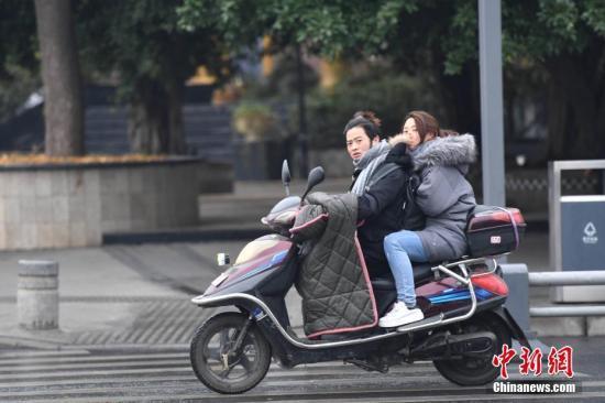 资料图:市民骑行在寒风中。