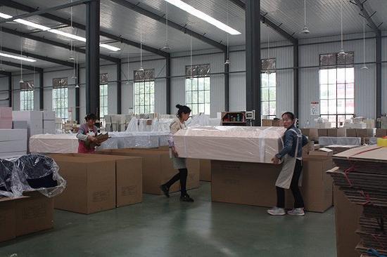 云龙木雕厂,两个女工在搬运棺材。图片来源:杨立赟