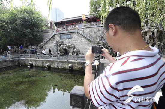 一位市民在给黑虎泉拍照