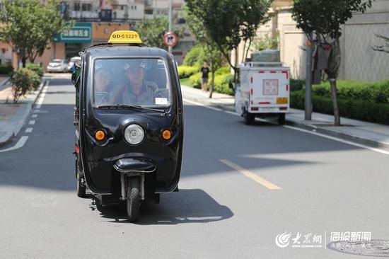 丈夫渠伟盈驾驶电动三轮车载着妻子去送快递
