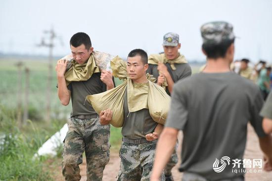 为了加快速度,救援人员甚至扛着两袋沙袋,负重前行。