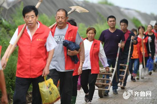 村民们带着铁锹,推着小车,赶往决堤口。