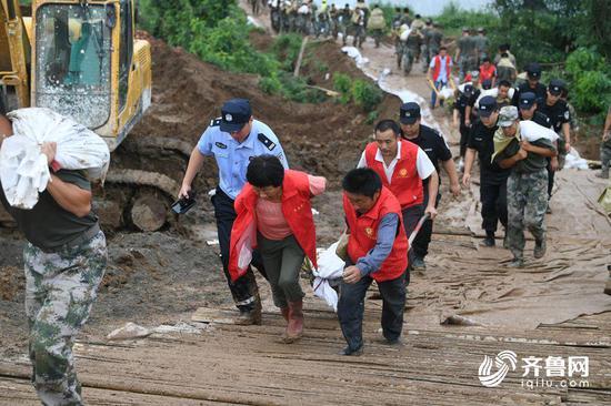 当地村民志愿者也加入抢修的队伍,一起帮忙运输沙袋。