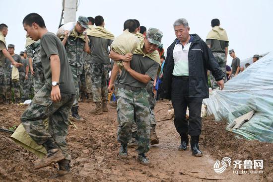 武警官兵肩上系着麻袋,防止在搬运过程中划伤。