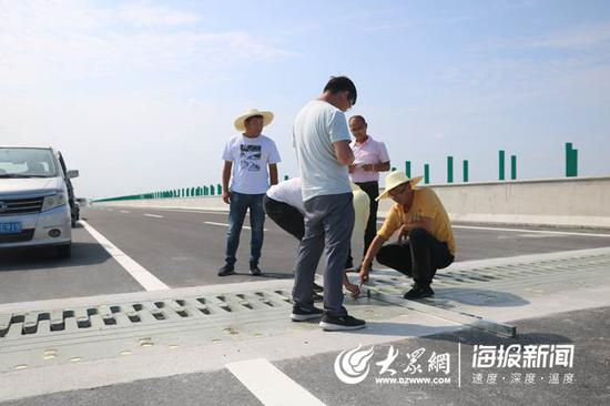 技术工人正在测量伸缩缝与桥面的高差