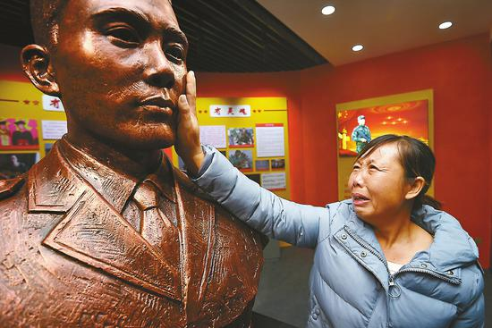 在王成龙的雕塑前,母亲管修梅泣不成声。
