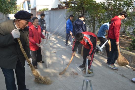 殷树山带领学生志愿者清扫辖区卫生死角(资料图)