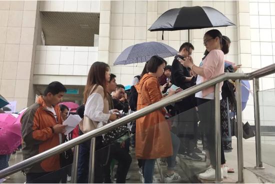 △资料图:2018年度湖北省公务员考试某高校考点,考生冒雨参加省考。