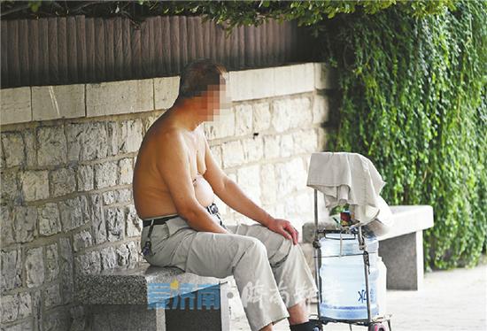 7月4日,在护城河黑虎泉段,一位市民赤裸上身在户外纳凉。