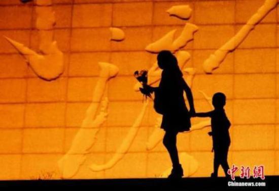 ↑资料图:母亲手持康乃馨拉着孩子。杨华峰 摄