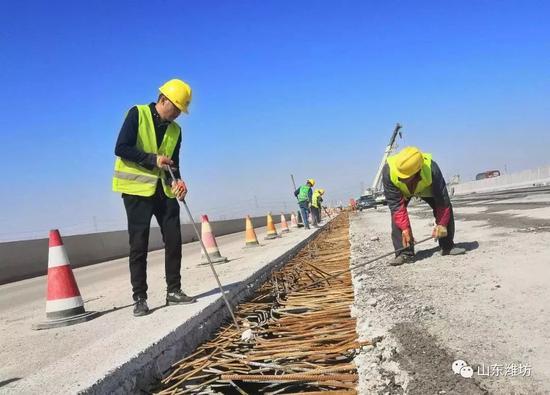 在弥河大桥,施工人员对新桥面和旧桥面连接处的钢筋进行取直。