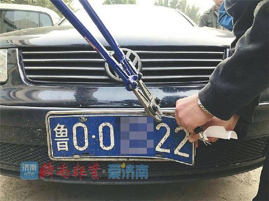 一辆鲁O车现场拆牌 记者谢苗苗 摄