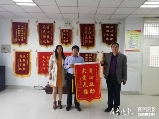 周某静(左一)与周某勇(右一)为滨州市救助站送去锦旗以表感谢