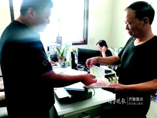 历下区住房保障和房产管理局工作人员将支票交给业主代表。