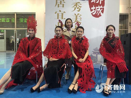 四位身材纤细的模特把剪纸穿戴上身现场走秀,吸引了一大批观众驻足拍照。