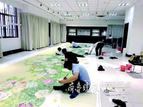 《锦绣春光》巨幅工笔牡丹画制作时的情景。巨野书画院供图