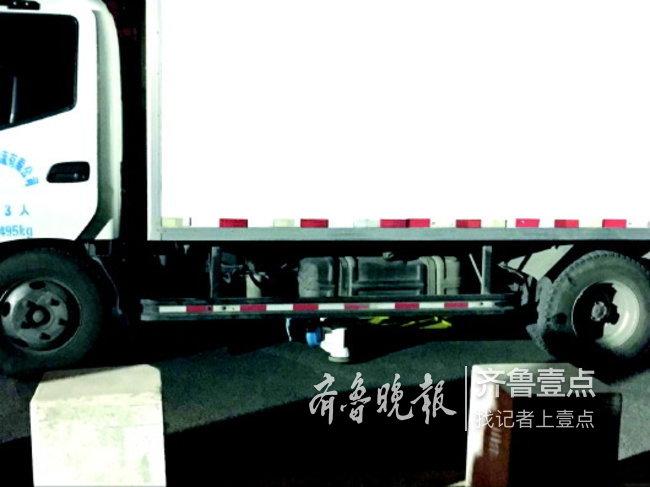 蓝白相间的童车躺在了货车下。 齐鲁晚报·齐鲁壹点记者 时培磊 摄