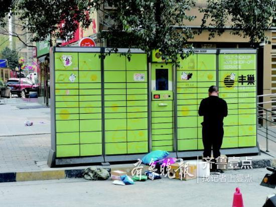 济南某小区内一名快递小哥在向快递柜里放快件。