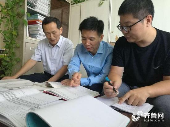 吕关仁(中)与工务技术人员讨论线路维护技术科研课