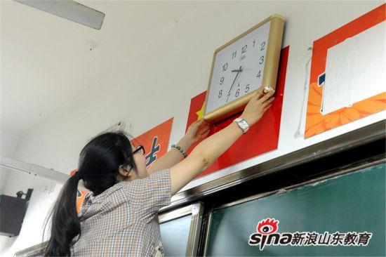 吴新颖老师将检查完毕的钟表悬挂在考场教室讲台正上方。