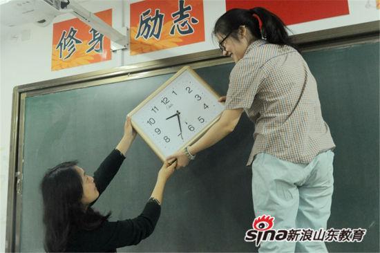 王志会、吴新颖两位监考老师整理考场,检查钟表运行情况,更换新电池。