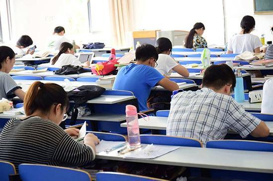 """""""考研族""""奋战暑期,自习室筑书""""墙""""。视觉中国 图"""