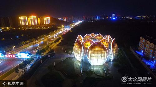 2017年9月12日,航拍济南万达文体旅游城展示中心首个荷花造型建筑夜色中悄然绽放,灯光辉煌,景色怡人。
