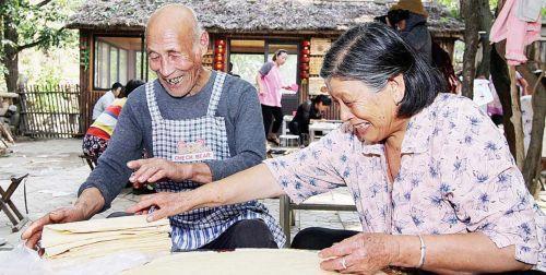 趁着游客还没上桌,老两口准备椿树沟杂粮煎饼。 本报记者 邱明 摄