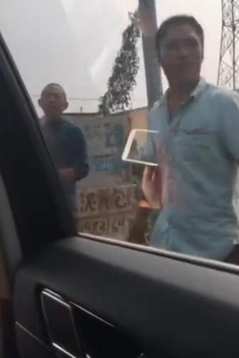 """两人在阻挡车辆的绕行村内道路时发现了""""商机"""",向绕路车辆索要钱财作为""""过路费"""",不然不让车辆通行。(视频截图)"""