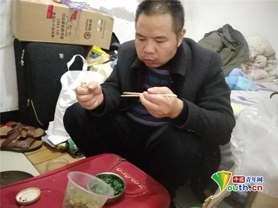 赵玉民在10平米的地下室内吃饭,吃的是生韭菜和花生渣。王庆龙 供图