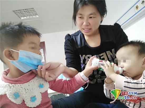 两岁姐姐小欣垚给一岁患病弟弟小冠豪喂奶补充营养。王庆龙 供图