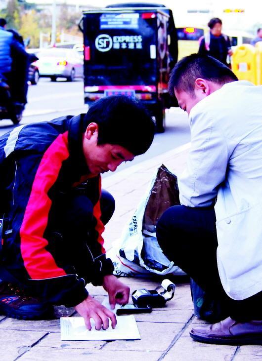 9日,济南街头一快递员为省时间,就地办理业务。齐鲁晚报记者 周青先 摄