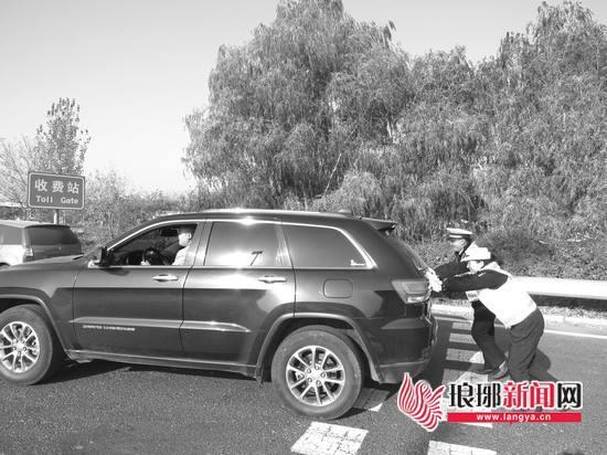 民警帮忙将故障车推离高速。