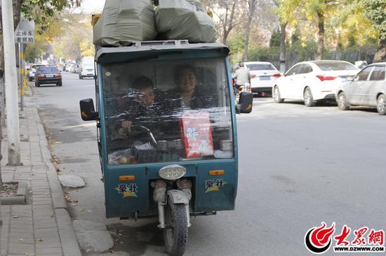 位于即丘路与平安路交会处,小李夫妇两人送走一波快递后,拥在狭小的快递车厢内,赶往下一个小区派件。