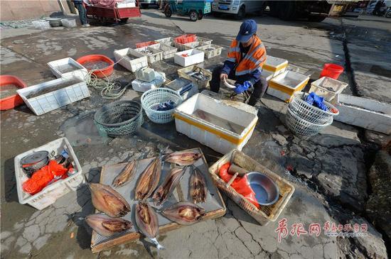 2017年11月12日,青岛市小港码头,渔民为顾客制作定制的鱼干。