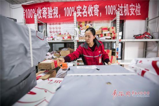 女站长陈杰正在整理刚刚卸载的快递件。