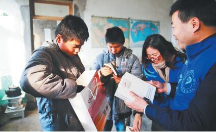 志愿者将书籍送到双胞胎兄弟胡安圣、胡安奇手中。