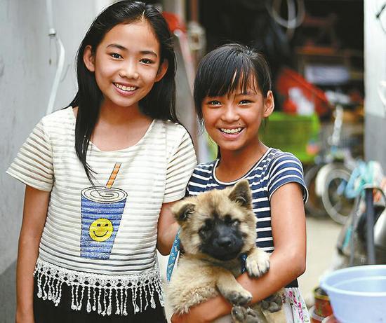刘伊婷(右)抱着捡来的小狗,和姐姐刘伊玲在一起。