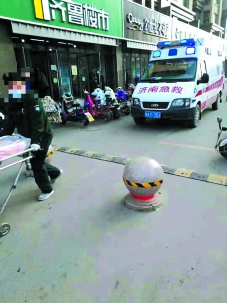 救护车被隔离墩挡住,救护人员只能用担架将孕妇抬到车上