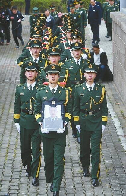 武警官兵手捧王成龙烈士的遗像