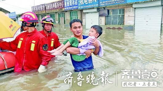 聊城暴雨救援中,高唐消防员抱起被困的孩子蹚过深水区。 消防供图