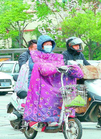 市民们把已经收起的冬衣又穿上了。    记者 周青先 摄