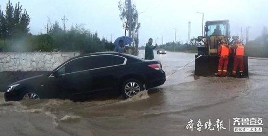 济南大雨致轿车被困桥下积水中 消防员借助铲车救人