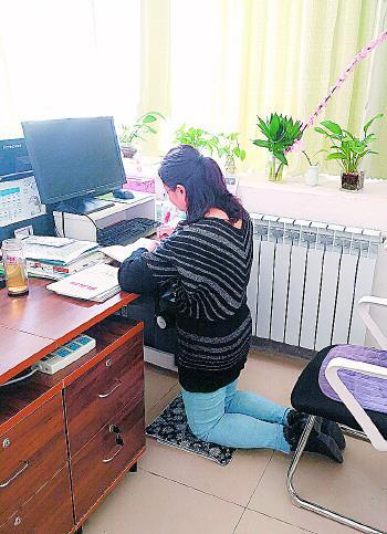 """杨老师在办公桌前""""跪着""""批改作业。"""