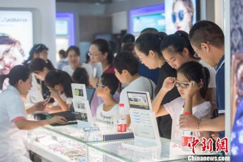 资料图:小学生们在柜台前挑选眼镜样式。韦亮 摄