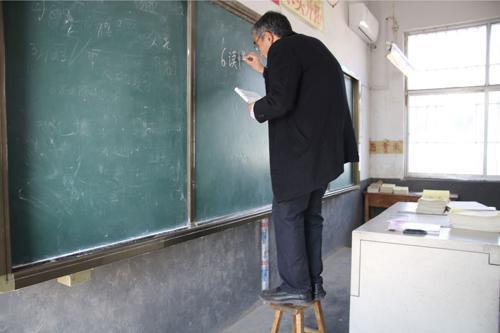 刘玉军踩在板凳上写板书